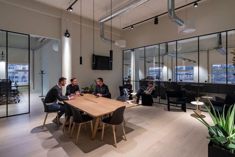Office con tres hombres haciendo el café en una mesa y dos descansando en unos sillones al fondo