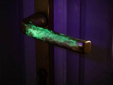 Pomo de una puerta iluminado con luz ultravioleta para detectar virus