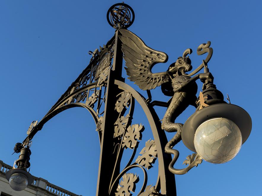 Farola de metal forjado con un dragón sosteniendo la bombilla