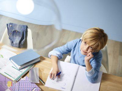 Niño haciendo los deberes bajo la luz deEyeConfort de Philips Signify
