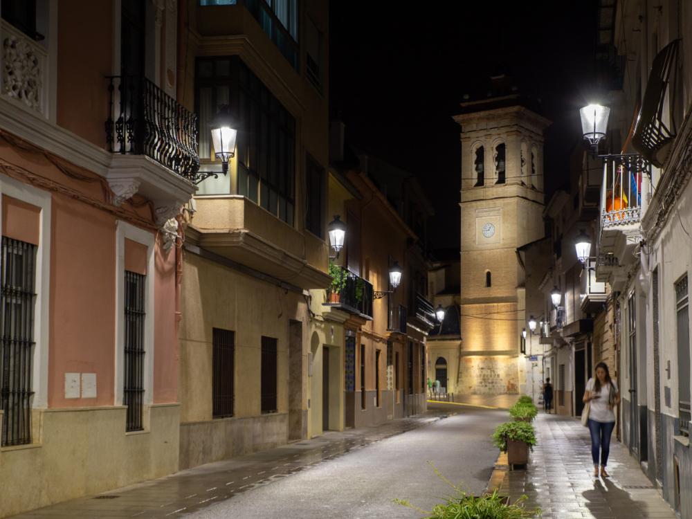 Calle del municipio de Torrente iluminada por la noche con las soluciones led de Schreder, al fondo un campanario.