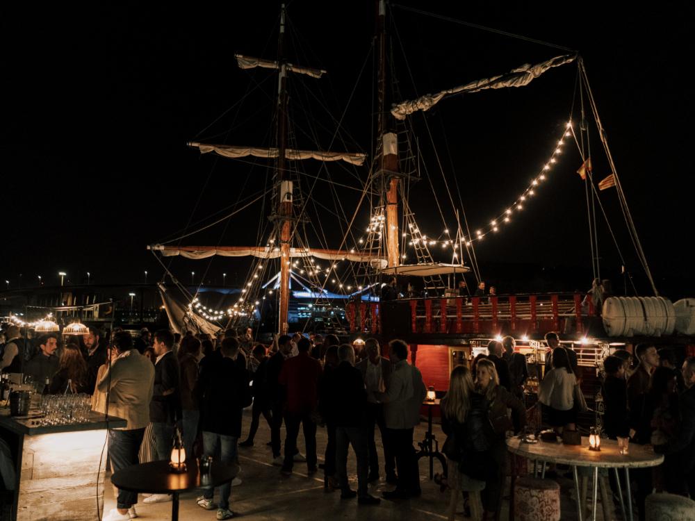 Imagen del evento en el Puerto de Barcelona con el barco iluminado de fondo