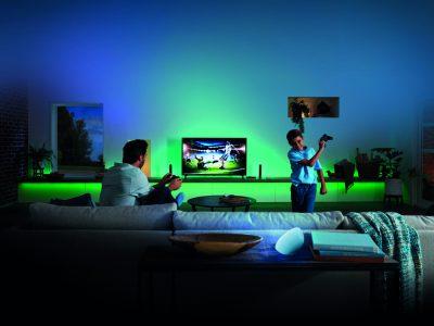 Padre e hijo jugando a videojuegos y Philips Hue HDMI Sync Box