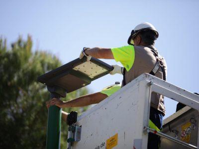 Operario instalando una farola solar de Signify en Sevilla