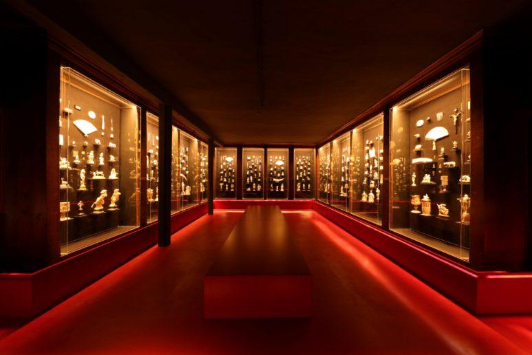 Ivory Museum. sala roja rodada de expositores de cristal iluminados y un banco central.