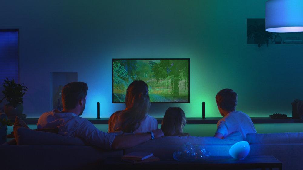 Familia en el salón viendo la tele con iluminación Philips Hue