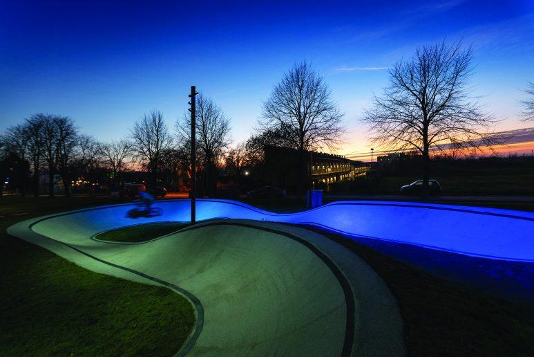 The Musicon Path, ganador de iluminación de exteriores. Un camino rodeado de árboles iluminado en azul, al atardecer.