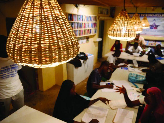 The Vessel, mención especial. Primer plano de una lámpara de mimbre que ilumina una mesa de personas estudiando.
